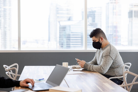 Businessman in face mask using smart phone in highrise coworking space