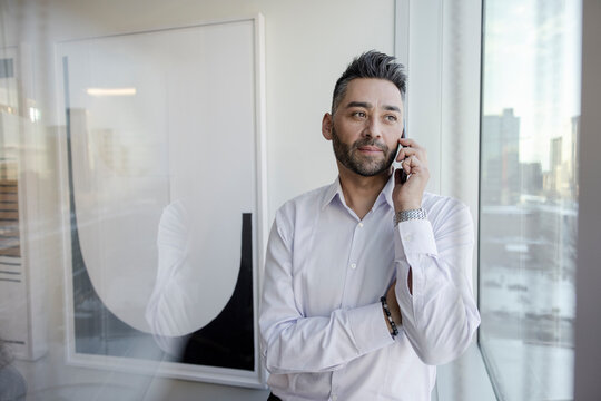 Businessman talking on smart phone at office window