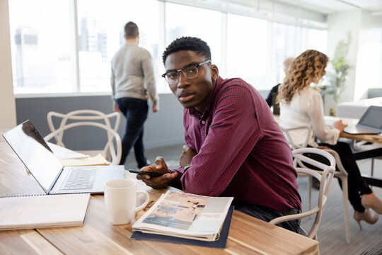 Portrait young businessman with smart phone in coworking space