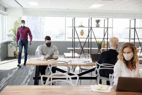 Business people in face masks working at distance in coworking space