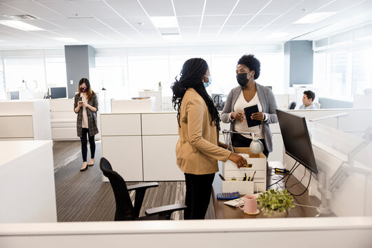 Businesswoman greeting new hire with box in office cubicle