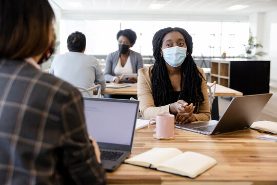 Businesswomen in face masks talking at laptops in coworking space
