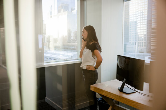 Young woman talking on smart phone at sunny highrise office window