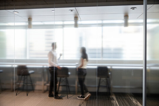 Business people talking behind conference room glass in office