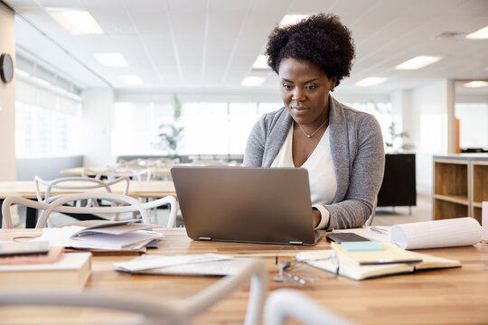 Businesswoman working at laptop in coworking space