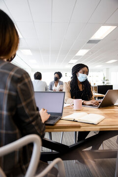 Businesswoman in face mask working at laptop in coworking space office