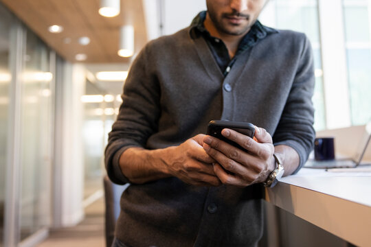 Close up businessman using smart phone in office