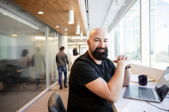 Portrait confident businessman with beard working at laptop in office