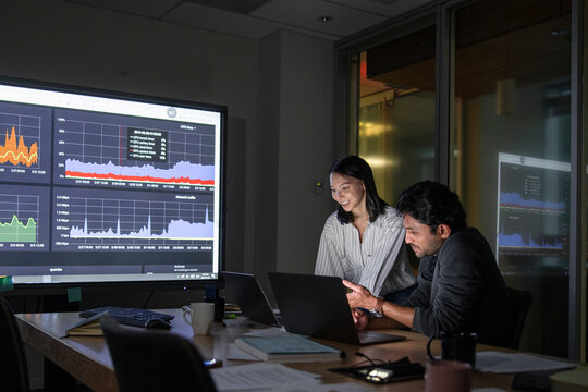 Business people working late preparing data in dark conference room