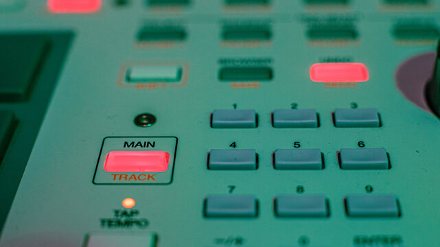 Macro details of a drum machine under colored lights.