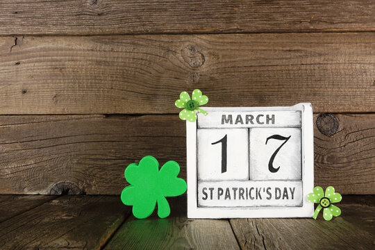 St Patrick Day displayed on a rustic shabby chic perpetual calendar with shamrocks against a dark wood background