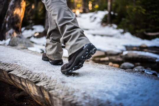 person walking in snow over log bridge in mountains