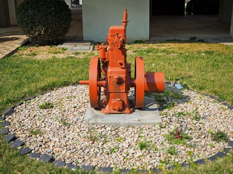 Old vintage 4 Stroke Stationary Engine painted and used as a decorative object in a garden,surrounded with pebbles