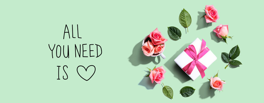 All you need is love message with a gift box and roses - flat lay