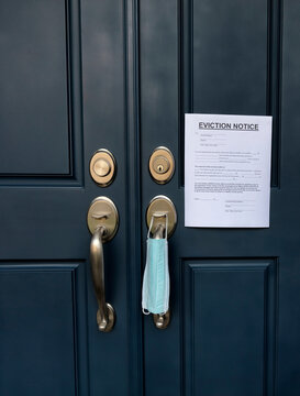 Home front door with eviction notice and facemask for renter in default during coronavirus pandemic