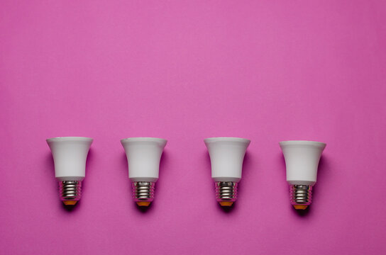 Four LED lamps without diffusers on a pink background.