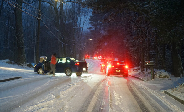 Vehicles waiting in line on the residential road after snow and accident