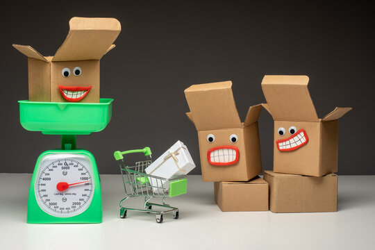 Open boxes next to green scales. Cardboard boxes are weighed on a vintage scale. Concept of sending parcels by weight. Weighing goods before sending them by mail. Weighing for transport.
