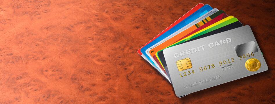 マホガニー調のテーブルに置かれた色々なクレジットカード