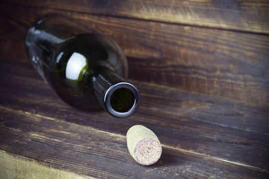 Lying empty wine bottle with cork nearby on plank wooden surface