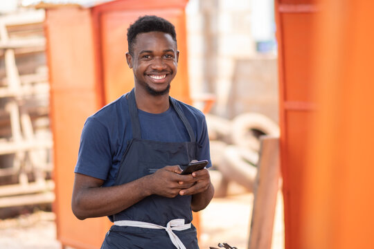 young african carpenter smiling while using his phone