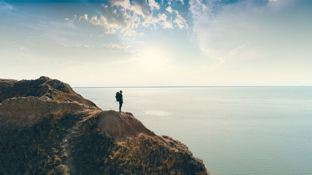 The hiker standing on a mountain on the sea sunshine background