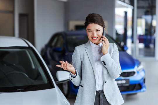 Smiling female car seller having phone conversation with a client and convincing him to buy a car. Car salon interior.