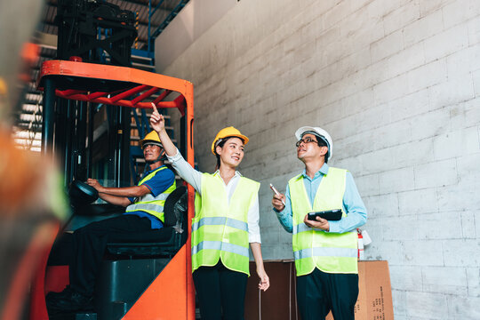 Working Team at warehouse. asian woman warehouse workers and Manager use Tablet Information to further placement in storage department. background driver at Warehouse forklift loader works with goods