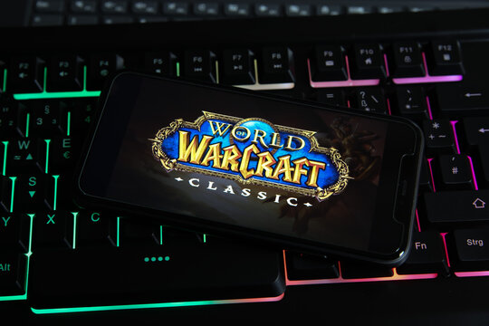Viersen, Germany - January 9. 2021: Closeup of smartphone screen with logo lettering of online game world of warcraft on illuminated computer keyboard