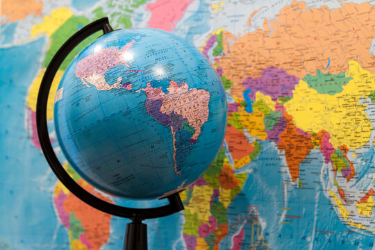 Mainz, Germany - November 14, 2017: Closeup of a globe with asia and africa and a world map with north and south america on the wall in classroom