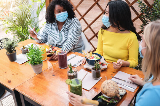 Young multiracial people talking in restaurant outdoors while wearing safety masks - Focus on asian girl