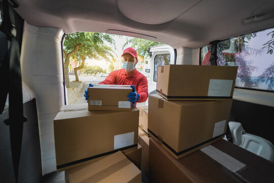 Delivery man picking up cardboard box from van during coronavirus lockdown - Focus on face