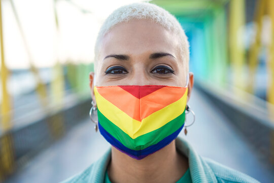 Portrait of young lesbian wearing rainbow flag pride mask - Focus on face