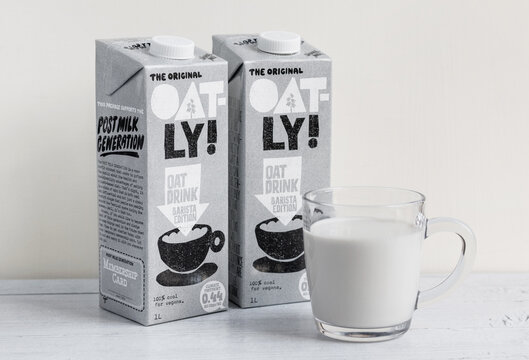 Oatly milk cartons and glass of oatly milk on a wooden table. Oatly is a dairy free vegan milk alternative - London / UK - September 2nd 2019