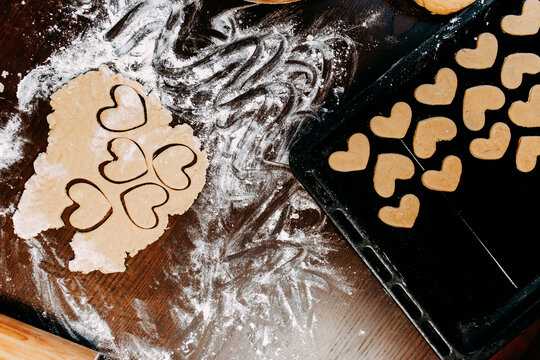 Cookies in shape of heart for the Saint Valentine's Day. Dough, flour, baking pan, round wooden cutting board and rolling pin on the table.
