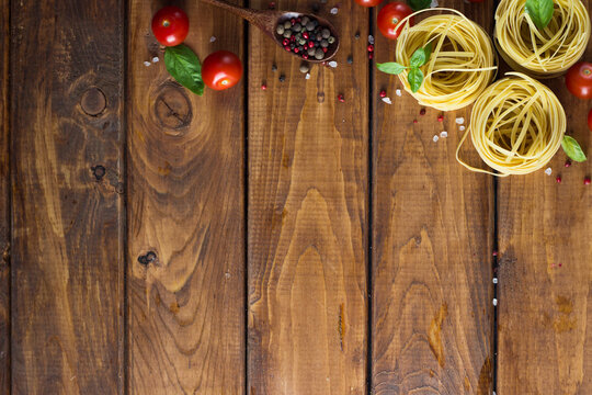 Marinara pasta ingredients lie on a wooden table. raw tagliatelle with spices and small cherry tomatoes