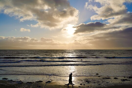 girl walking on the beach at sunset silhoette