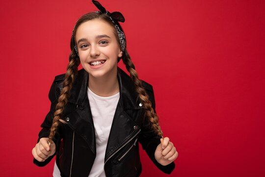 Charming positive smiling brunette little female teenager with pigtails wearing stylish black leather jacket and white t-shirt standing isolated over red background wall looking at camera