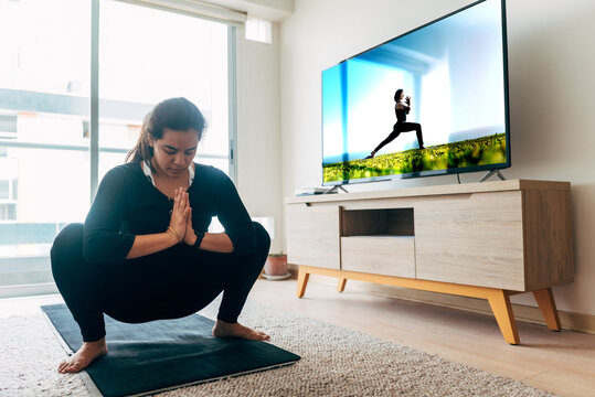 Latin woman follows yoga class at home on smart TV
