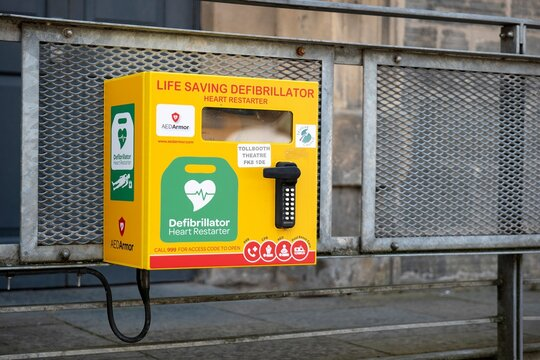 Life Saving Defibrillator (Heart Restarter) yellow rescue box in the streets of Striling city in Scotland, United Kingdom