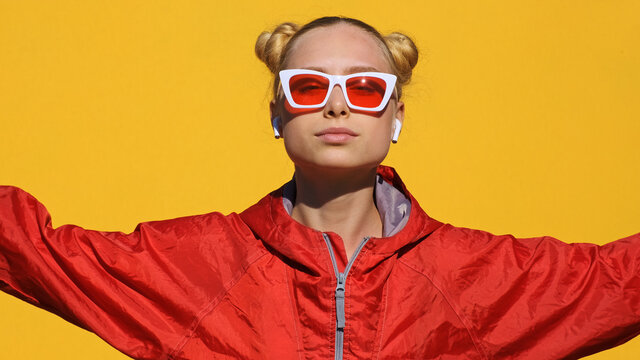 Portrait of happy teen girl blonde in airpods in stylish sunglasses, red hoodie smiles, dances, rhythmically shaking his head camera on yellow background summer. Emotions. Girl dancing