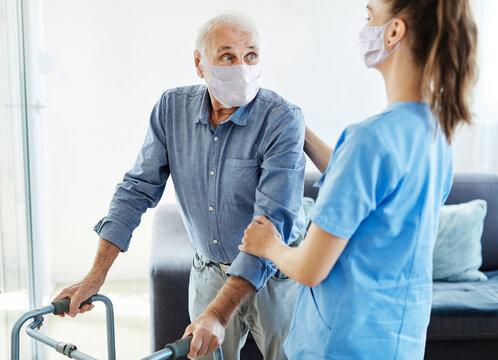nurse doctor senior care caregiver help walker assistence retirement home nursing man virus mask corona