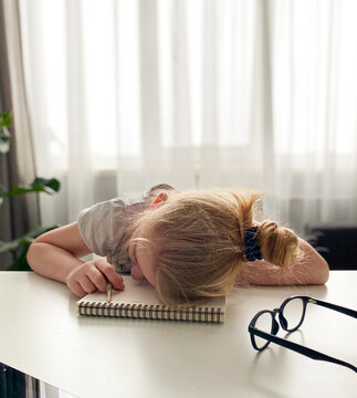 schoolgirl was tired of home schooling and fell asleep at the table on a notebook with a pencil in her hand . Distance learning during the coronavirus.