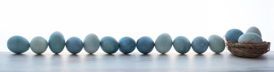 Blue pastel dyed easter eggs in a row on gray surface. Horizontal background for easter greetings with space for text.