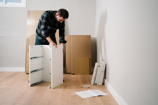 Portrait of man assembling furniture. Do it yourself furniture assembly.