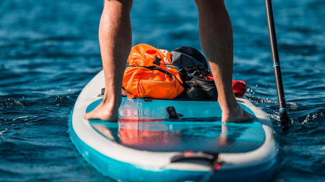 Young athletic man paddling on a SUP stand up paddle board in blue water sea in Montenegro