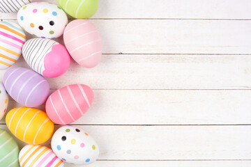 Colorful Easter Egg side border. Above view against a white wood background. Copy space.