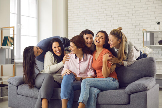 Group of happy friends having fun and enjoying free time together. Carefree young women sitting on sofa at home, laughing and fooling around. Concept of friendship, sharing happiness, mutual support