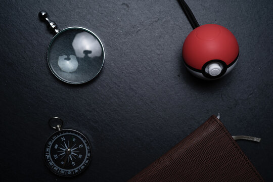 KUALA LUMPUR, MALAYSIA - JUNE 13TH, 2019 : A Poké Ball Plus on a black slate stone, you can bring your Pokémon adventure into the real world with an accessory that fits in the palm of your hand