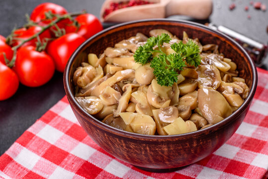 Fresh delicious spicy canned mushrooms with spices and herbs in ceramic dishes